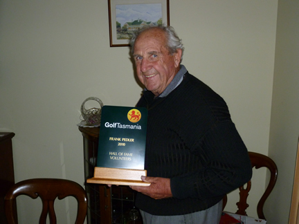 This shows a photo of Frank in his living room looking proud with his Golf Tasmania hall of fame trophy